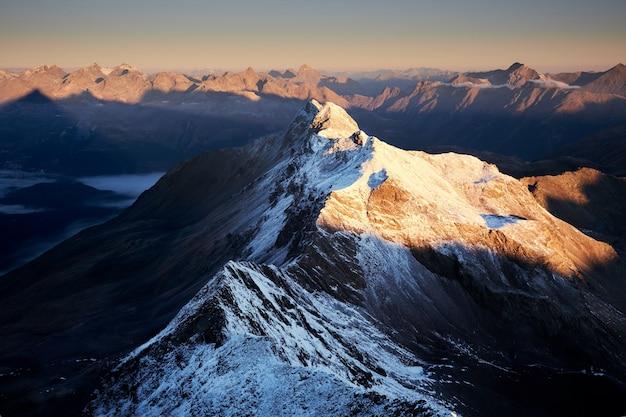 Foto aérea de montanhas nevadas, com um céu claro no dia