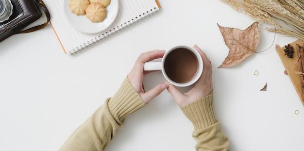 Foto aérea de mulher segurando a xícara de chocolate quente no outono espaço de trabalho com espaço de cópia