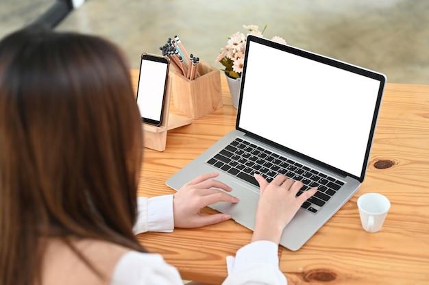 Foto aérea de mulher trabalhando com laptop e smartphone na mesa de madeira.