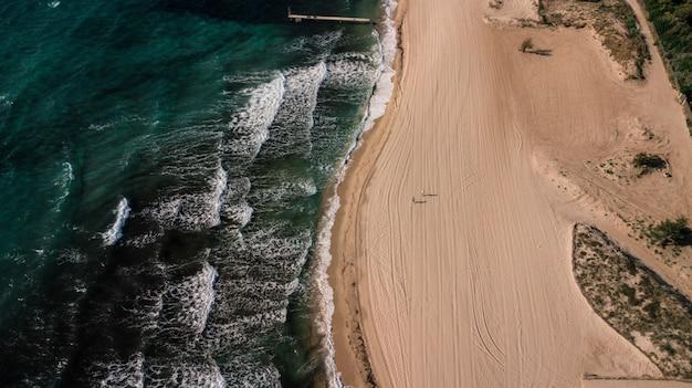 Foto aérea de ondas do oceano verde com uma praia arenosa