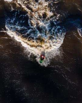 Foto aérea de ondas espumosas do oceano e um homem em um caiaque segurando o remo durante o pôr do sol