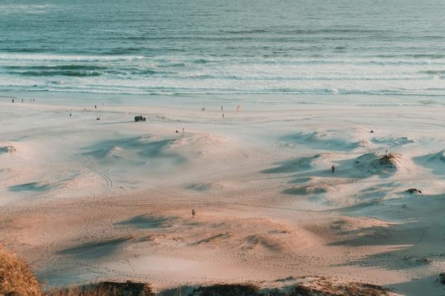 Foto aérea de pessoas vistas à distância na praia durante o pôr do sol
