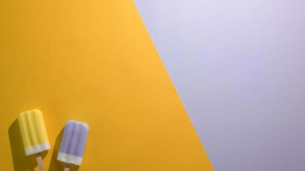 Foto aérea de picolés de sabor de limão e mirtilo e espaço da cópia no plano leigos fundo verde e roxo