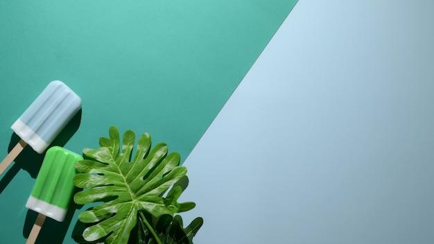 Foto aérea de picolés de sabor limão e framboesa azul sobre fundo verde e azul leigos