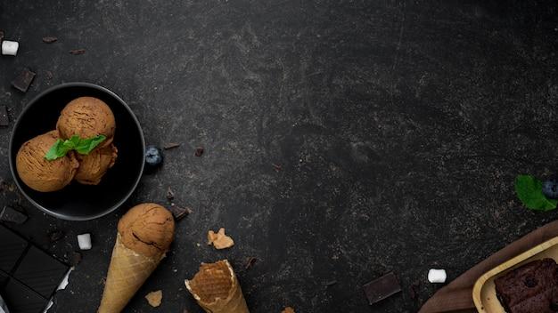 Foto aérea de sobremesa de verão com casquinhas de sorvete de sabor chocolate na mesa escura