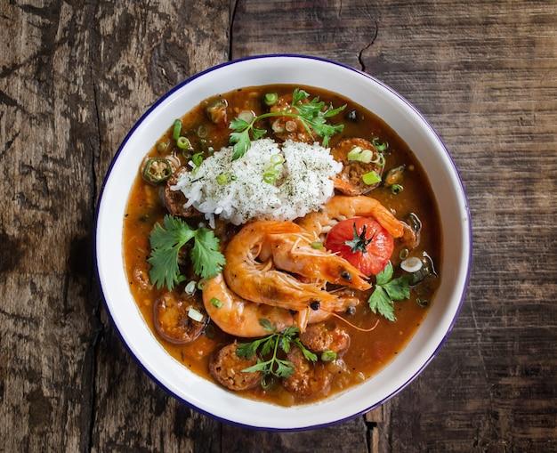 Foto aérea de sopa com camarão e legumes deixa em uma tigela branca