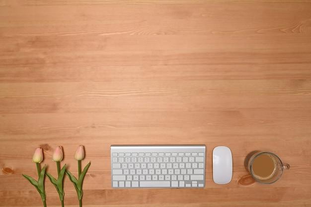 Foto aérea de teclado sem fio, tulipas cor de rosa e xícara de café em fundo de madeira.