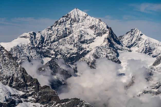 Foto aérea de tirar o fôlego das montanhas rochosas cobertas de neve sob um céu panorâmico