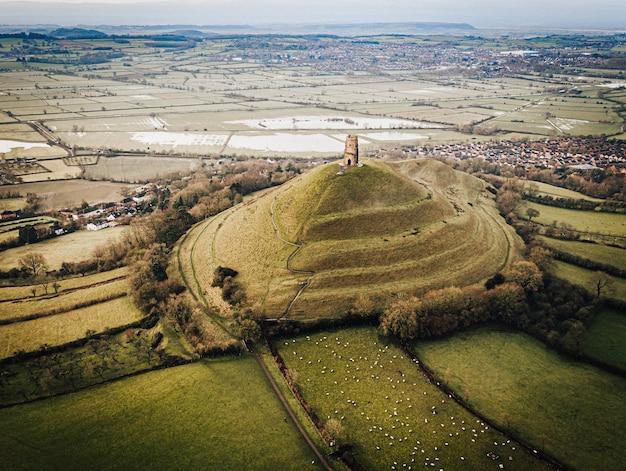 Foto aérea de um antigo castelo no topo de uma colina coberta de grama no meio de campos verdes