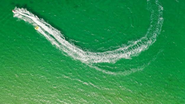 Foto aérea de um barco com uma pessoa surfando em uma corda ligada a ele