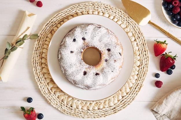 Foto aérea de um bolo de anel com frutas e pó em uma mesa branca com fundo branco