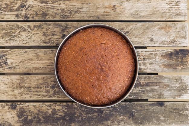 Foto aérea de um bolo delicioso assado em um molde redondo em uma superfície de madeira