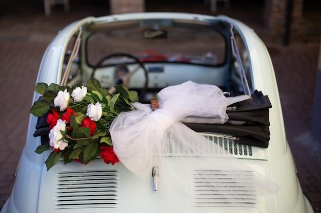 Foto aérea de um buquê de flores colocado no topo do carro com um fundo desfocado