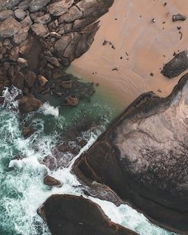 Foto aérea de um canal de água bonita com pedras e pessoas ao redor