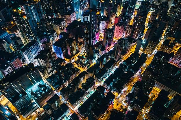 Foto aérea de um cenário urbano com prédios altos, espalhando a luz durante a noite