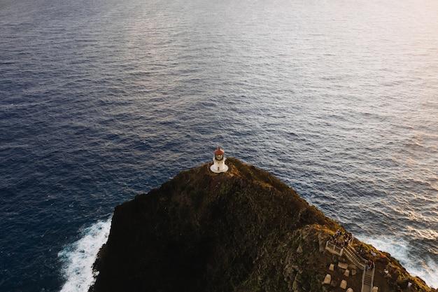 Foto aérea de um farol no topo de uma falésia em mar aberto