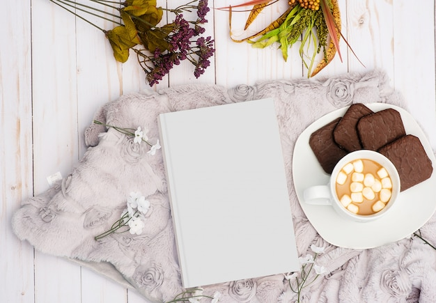 Foto aérea de um livro branco ao lado de uma bebida doce com biscoitos de chocolate num prato