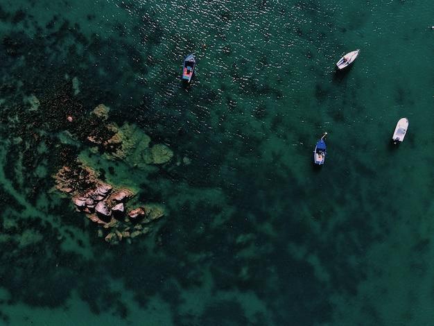 Foto aérea de um mar com barcos perto de uma pedra durante o dia