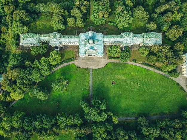 Foto aérea de um palácio abandonado na floresta. gramado verde, árvores, dia de verão. rússia, são petersburgo, peterhof. postura plana.