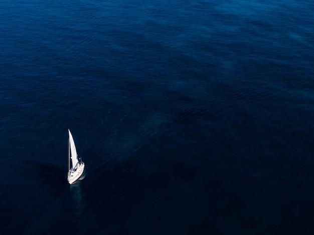 Foto aérea de um pequeno barco branco navegando no oceano