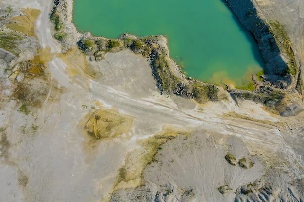 Foto aérea de um poço de argila com um enorme lago verde para extração de areia na carreira de granito