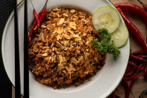 Foto aérea de um prato com arroz e legumes fatiados em um prato branco redondo