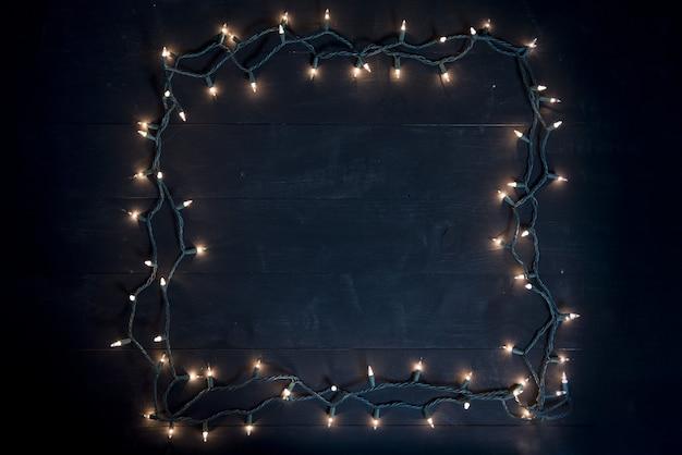 Foto aérea de um quadrado feito com luzes de natal em uma superfície de madeira