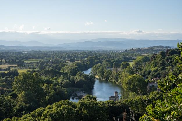 Foto aérea de um rio com uma igreja na margem cercada por árvores e campos. narbonne na frança