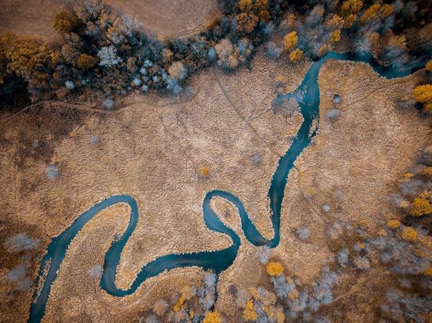Foto aérea de um rio no meio de um campo gramado seco com árvores ótimas para o fundo