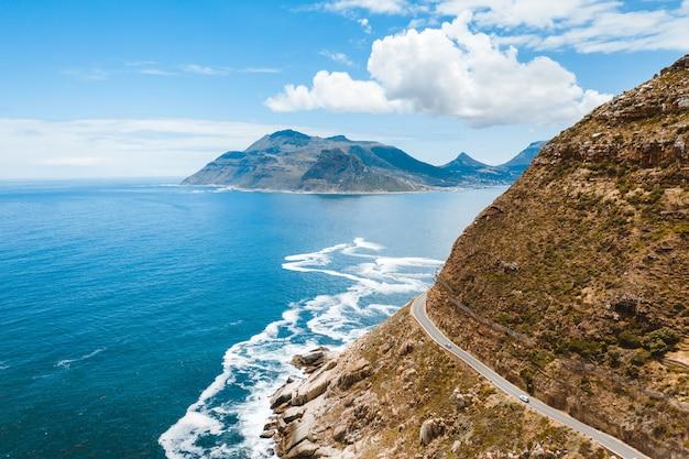 Foto aérea de uma bela estrada em uma montanha perto de um corpo de água durante o dia
