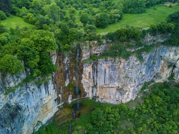 Foto aérea de uma cachoeira na bela montanha coberta de árvores