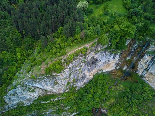 Foto aérea de uma cachoeira na bela montanha coberta por árvores