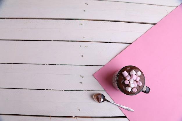 Foto aérea de uma caneca de chocolate quente com marshmallows e uma colher na mesa da cozinha