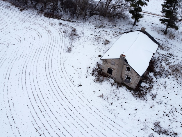 Foto aérea de uma casa rural com campos cobertos de neve