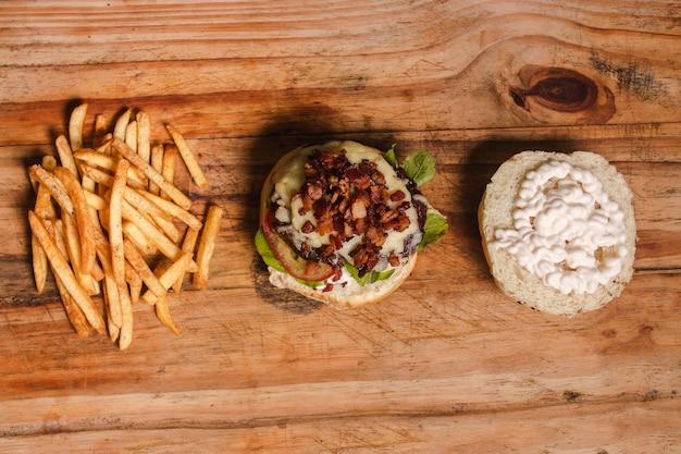 Foto aérea de uma combinação de batatas fritas e um hambúrguer dividido em cima de uma mesa de madeira.