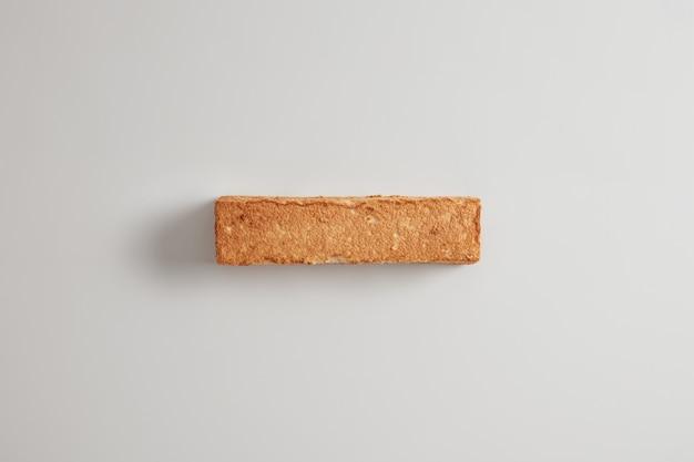 Foto aérea de uma crocante fatia de pão no fundo branco. produto acabado de cozer. conceito de alimentação e dieta saudável. fundo de comida. pão de trigo sarraceno sem fermento. itens de confeitaria para comer