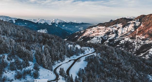 Foto aérea de uma estrada, atravessando montanhas nevadas cobertas por uma floresta de pinheiros