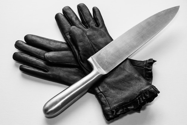 Foto aérea de uma faca de metal sobre luvas pretas em uma superfície branca