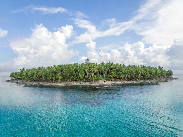 Foto aérea de uma ilha verde cercada por águas límpidas com nuvens no
