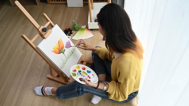 Foto aérea de uma jovem artista feminina está pintando na tela enquanto está sentada no chão de seu estúdio.