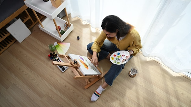 Foto aérea de uma jovem pintora está desenhando com tinta de pôster em sua oficina.