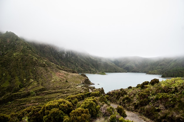 Foto aérea de uma lagoa rodeada por colinas verdes e montanhas arborizadas em um nevoeiro