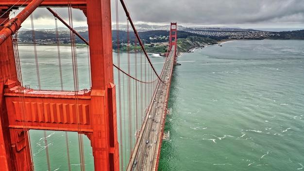 Foto aérea de uma longa ponte suspensa vermelha sobre um belo rio grande