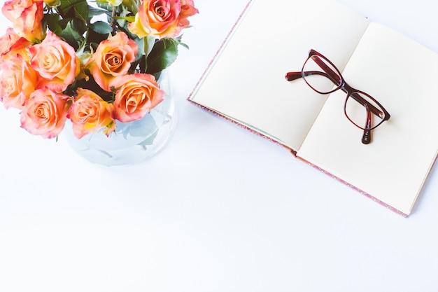 Foto aérea de uma mesa branca com rosas e um par de óculos em um caderno em branco