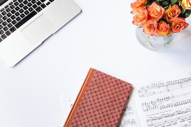Foto aérea de uma mesa branca com um caderno vermelho, algumas flores, uma partitura e um laptop