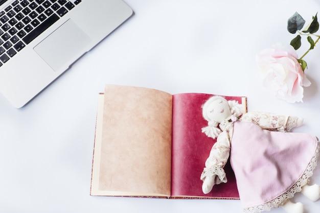 Foto aérea de uma mesa branca com uma boneca em cima de um caderno, uma flor e um laptop