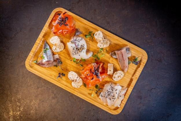 Foto aérea de uma mesa defumada em um fundo preto, frutos do mar, uma variedade de peixes e frutos do mar