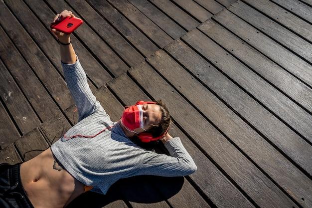 Foto aérea de uma mulher com uma máscara e fones de ouvido deitada em uma doca de madeira e tirando uma selfie