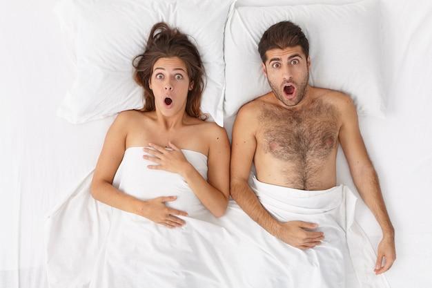 Foto aérea de uma mulher e um homem em choque emocional ficam na cama cobertos por um lençol, olhando com a boca aberta, trabalho adormecido ou vôo. casal familiar chocado acorda no quarto de hotel. amantes espantados