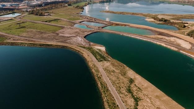 Foto aérea de uma paisagem cercada por montanhas e lagos com desastre industrial